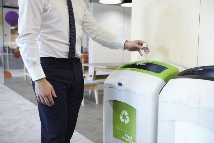 Mies lajittelee kierrätysmerkkien mukaan