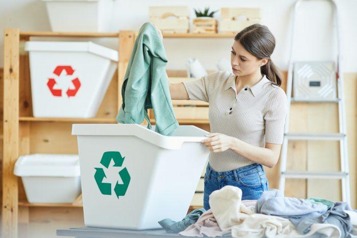 Nainen lajittelee vaatteita kierrätyskeskukseen